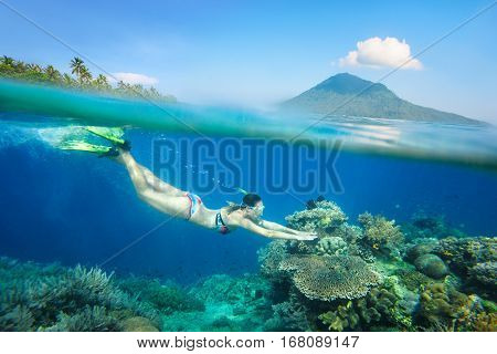 Snorkeling woman over a beautiful coral reef in the background the island of Bunaken North Sulawesi. Indonesia.