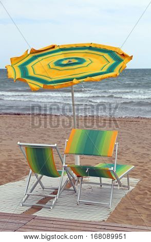 Rough Sea And The Beach With An Umbrella In The Wind With Two De