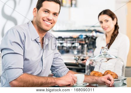 Portrait of handsome young man looking at camera during breakfast indoors in a cozy location