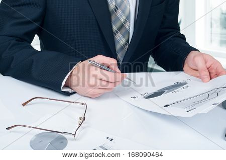 Businessman analyzing financial figures denoting the progress in the work of the company.