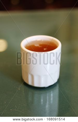 Green Tea. Chinese hot green tea. Hot Tea being poured into a white tea cup