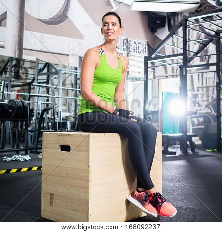 Woman sitting on box in functional training gym after exercising