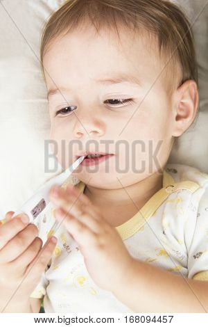 Sick baby measuring temperature with thermemother