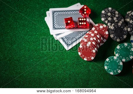 Close Up Casino Chips And Cards On Green Gamble Table.