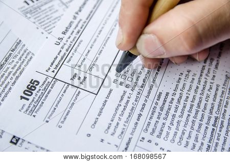 Person completing 1065 tax form close up