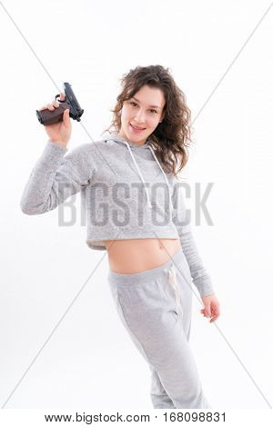 Young girl in a tracksuit with a gun. Beautiful young woman is aiming a revolver