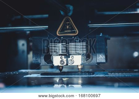 3d printer printing black flat shapes on a dark background close-up. Image of automatic three dimensional 3d printer performs plastic modeling in laboratory.