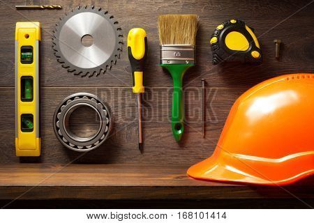 tools and wooden shelf at brown background