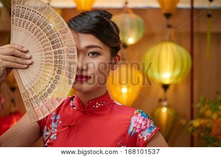 Beautiful Chinese woman covering half of her face with fen