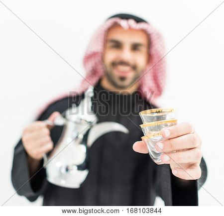 Gulf Arabian young man with traditional welcome hospitality coffee
