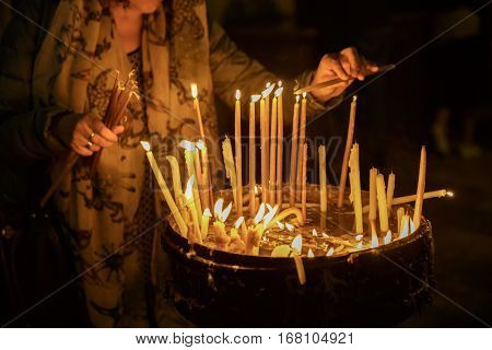 Religious Christian woman lights a candle in the Holy Sepulchre on Mount Calvary Jerusalem Israel