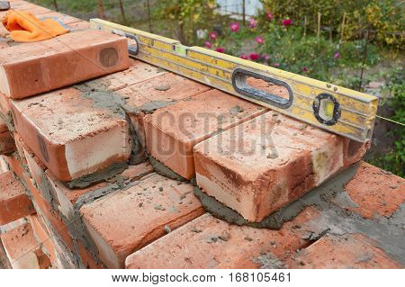 Bricklaying with Spirit Level to Check New Red Brick House Wall Outdoor. Basic Bricklaying.