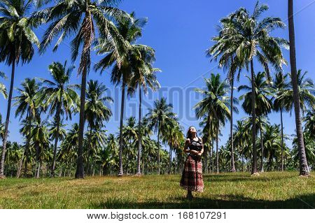Girl on a palm plantation. Girl in dress on the palm plantation