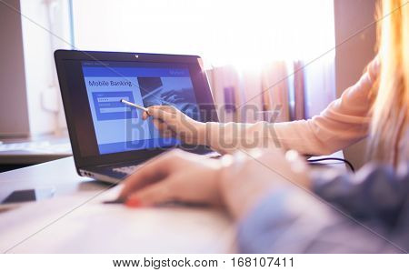 Close up of woman hand using on line banking. Teaching client to log in to a bank account typing password. Business, financial and secure payment concept.