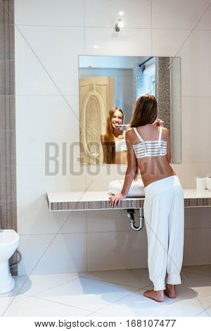 Pre teen girl brushes her teeth in the hotel bathroom interior. 10 years old child washing in the morning, lifestyle photo.