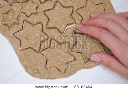 Woman Cutting Christmas Cookies From Rye Dough With Star Shaped Cutter