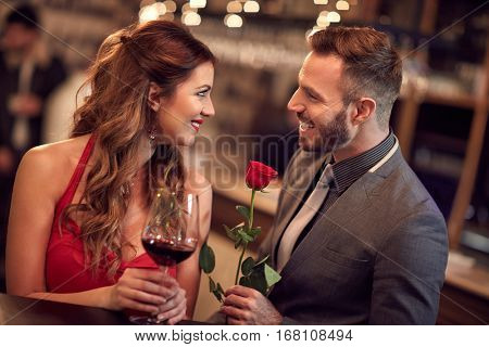 Handsome man giving rose to attractive lady