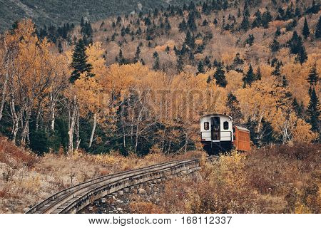 MT Washington, NEW HAMPSHIRE - OCT 13: Tourism train at mountain range with foliage on October 13, 2015 in New Hampshire. Mt Washington is the highest peak in Northeastern America.