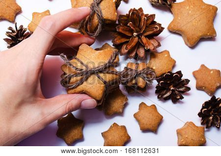 Female Hand Holding Homemade Rye Cookies Star Shaped Stack Tied With Brown Rope On White Background