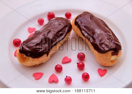 Chocolate eclairs on plate on white background sprinkled with red currant berries and hearts.