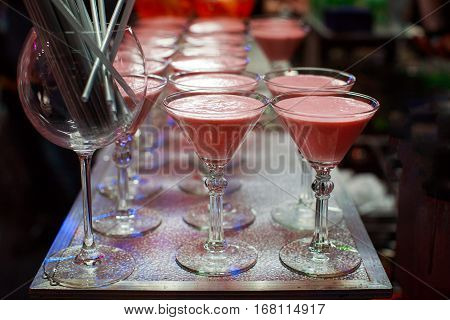 Glasses with rose Smoothies coctails on the bar with cocktail tubules close-up