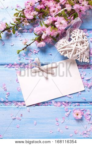 Sakura flowers decorative heart and empty tag on blue wooden background. Selective focus. Place for text. Flat lay. Top view. Shabby chic.