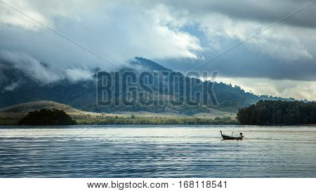 The rainy season in Asia. Boat on a background of mountains