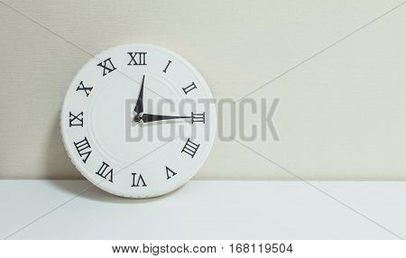Closeup white clock for decorate show a quarter past twelve or 12:15 a.m. on white wood desk and cream wallpaper textured background with copy space