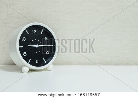 Closeup black and white alarm clock for decorate show a quarter past nine or 9:15 a.m.on white wood desk and cream wallpaper textured background with copy space