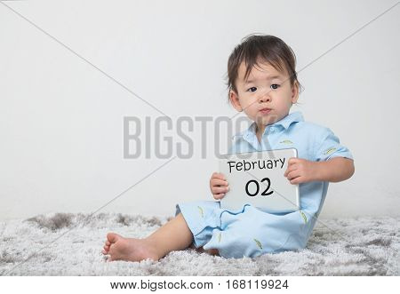 Closeup cute asian kid show calendar on plate in his hand in february 2 word on gray carpet and white cement wall textured background with copy space