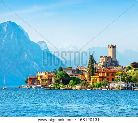 Ancient tower and fortress in old town Malcesine at Garda lake. Veneto region. Italy. High snowbound top mountains on background. Summer landscape with colorful houses green trees.