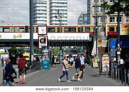 BERLIN, GERMANY - MAY 10: The busy and famous Alexander Square with pedestrians and passersby in fine weather near a subway bridge on May 10, 2016 in Berlin.