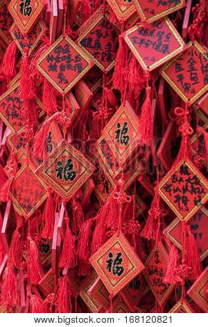 Photo of Traditional Red Wishing Envelopes with Handwritten Wish. Greeting Card Red Plate Hanging on Wishing Tree