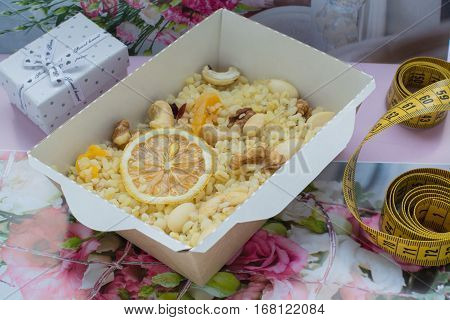 bulgur with nuts decorated with the dihydrogenated lemon in a craft box. The word loving and a box with a gift on a flower background. Healthy nutrition dish.