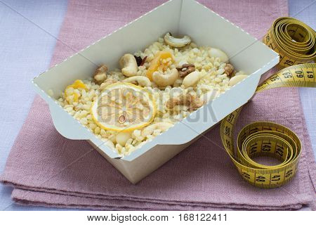 bulgur with nuts decorated with the dihydrogenated lemon in a craft box on a on a linen cloth with a centimetric tape. Healthy nutrition dish.