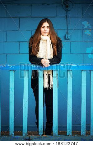 A young girl stands against a blue brick wall and leans on the railing. Long dark hair, scarf, white chunky knit