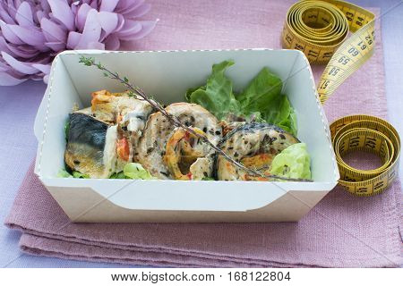 The beaters from the baked mackerel in a craft box on a on a linen cloth with a centimetric tape. Healthy nutrition dish.