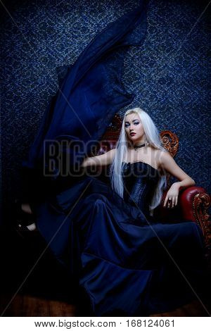 Gothic style. Beautiful young woman with long blonde hair and black make-up posing in long black dress in vintage interior. Antique castle style. Halloween.