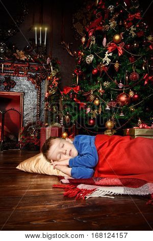Christmas concept. Cute little boy fell asleep under the Christmas tree waiting for Santa Claus. Time for miracles.