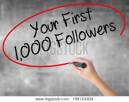 Woman Hand Writing Your First 1,000 Followers  With Black Marker Over Transparent Board