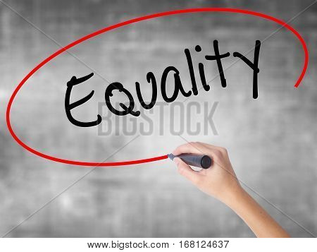 Woman Hand Writing Equality  With Black Marker Over Transparent Board