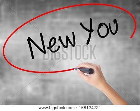 Woman Hand Writing New You With Black Marker Over Transparent Board