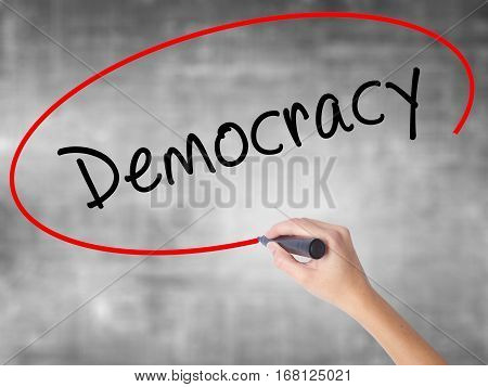 Woman Hand Writing Democracy With Black Marker Over Transparent Board
