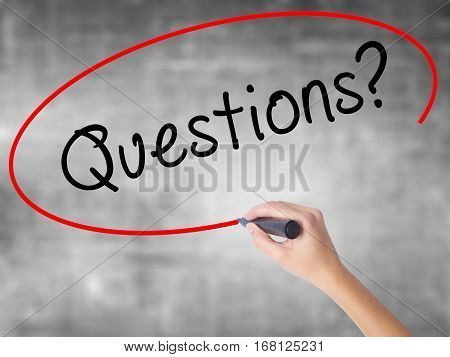 Woman Hand Writing Questions? With Black Marker Over Transparent Board