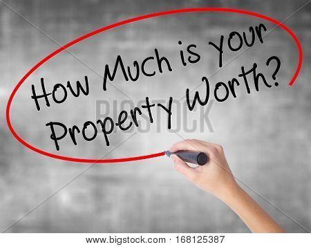 Woman Hand Writing How Much Is Your Property Worth? With Black Marker Over Transparent Board