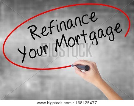 Woman Hand Writing Refinance Your Mortgage With Black Marker Over Transparent Board