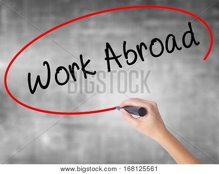 Woman Hand Writing Work Abroad With Black Marker Over Transparent Board