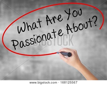 Woman Hand Writing What Are You Passionate About?  With Black Marker Over Transparent Board