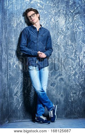 Happy young man in casual jeans clothes and spectacles posing by a  grunge background. Men's beauty, fashion. Optics style. Full length portrait.