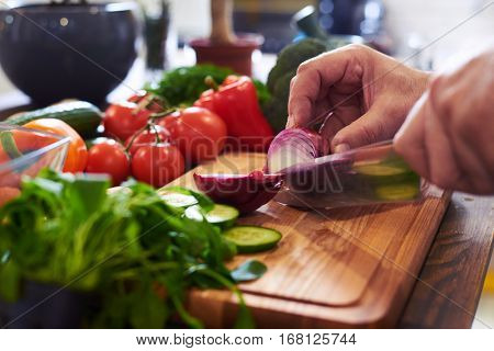 Side view of hands cutting an onion in the correct shape. Peeled red onion. Raw red onion cut in half with slices of cucumber